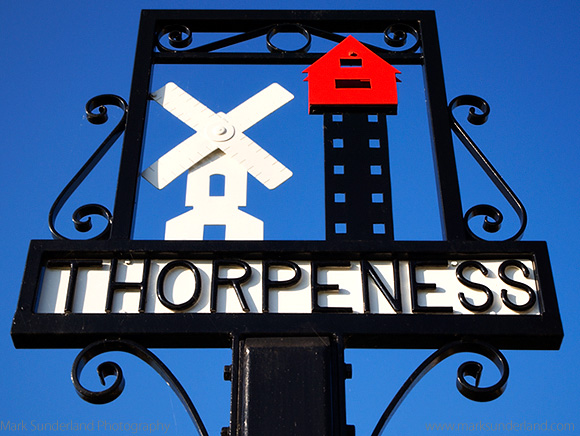 Thorpeness Village Sign showing the Windmill and House in the Cl