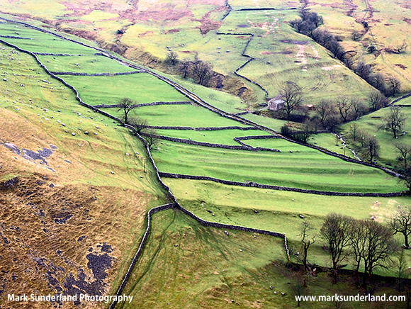 Meadows and Dry Stone Walls rise up the hillside at Gordale Scar Malham Yorkshire England