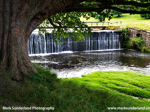 Dam on the River Skell forming the Ornamental Lake at Studley Park near Ripon North Yorkshire England
