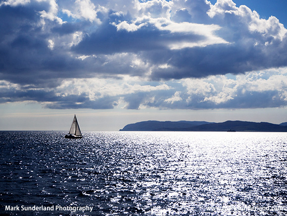 Yacht Sailing and Sunlight reflecting off the Sea in the Firth of Lorn with Mull beyond Argyll and Bute Scotland