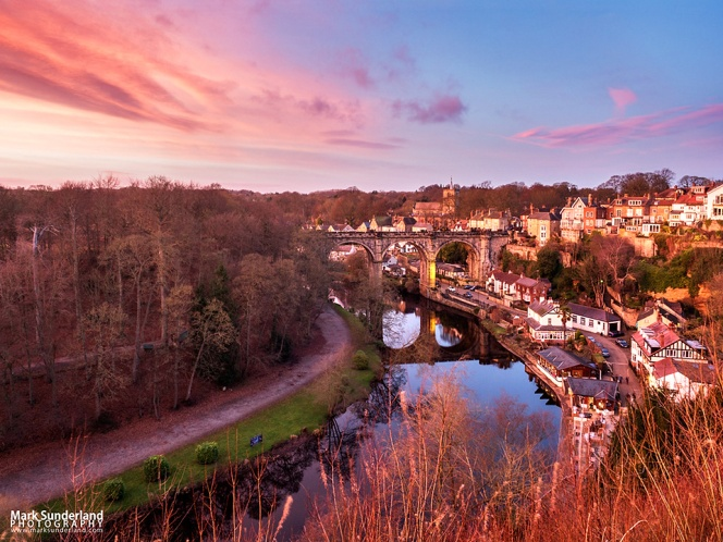 Pink sky at dusk over the Railway Viaduct from the Castle Grounds in Knaresborough