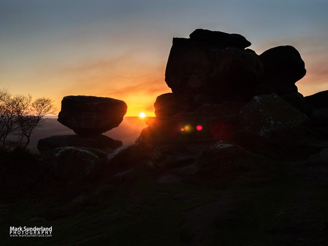 Gritstone rock formations silhouetted against a sunset sky at Brimham Rocks