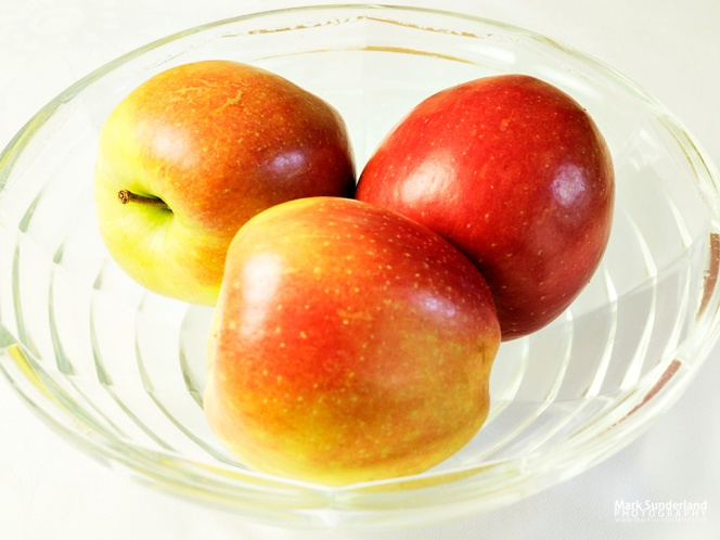 Three braeburn apples in a glass fruit bowl