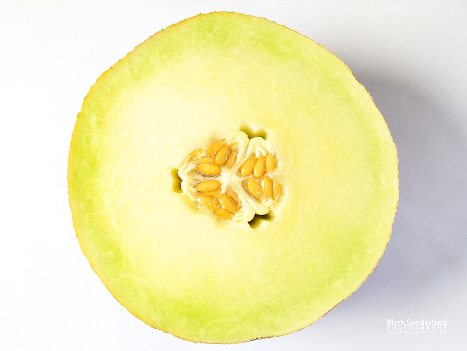 Half a fresh galia melon with seeds isolated on a white background