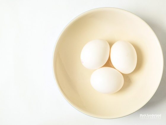 Three white eggs in a bowl offset on a white background with copy space